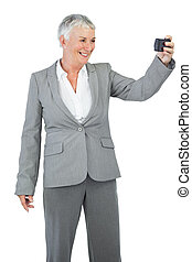 Businesswoman taking picture of herself on white background