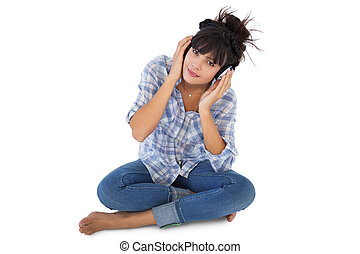 Cute young woman sitting on the floor listening to music on...