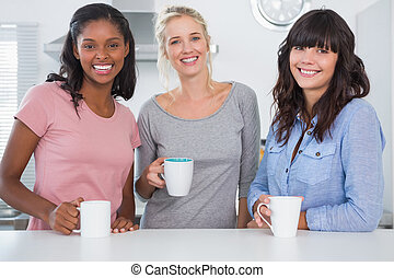 Friends having coffee together smiling at camera in kitchen