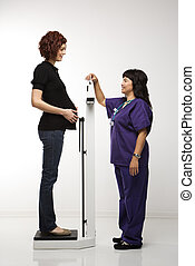Pregnant woman being weighed. - Pregnant Caucasian mid-adult...