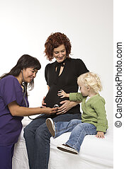 Pregnant woman having exam. - Nurse holding stethoscope on...