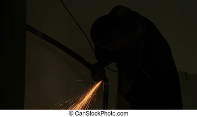 Sanding. Silhouette of a man shlishuyuschego metal pipe....