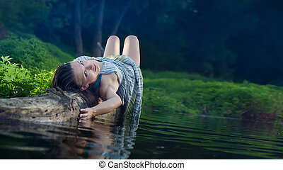 Pretty girl in cotton dress is laying on the log