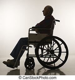 Man in wheelchair - Profile view of silhouetted Caucasion...