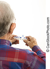 Man holding pill organizer.