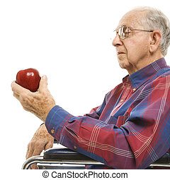 Elderly man holding apple. - Profile of Caucasion elderly...