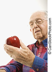 Elderly man holding apple. - Caucasion elderly man looking...
