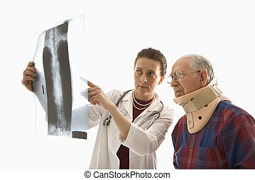 Doctor and injured patient - Mid-adult Caucasian female...