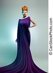 Fashion studio shot of beautiful woman in violet dress with...