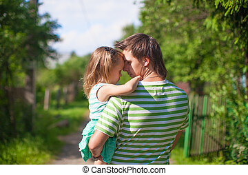 Young father with a daughter in the village outdoors