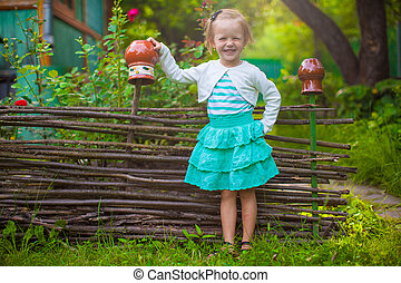 Adorable little girl standing near vintage wooden rural fence and smiling