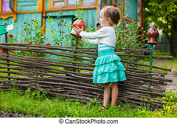 Adorable little girl standing near vintage wooden rural fence
