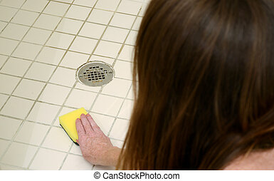 cleaning shower with scour pad - woman scrubbing shower...
