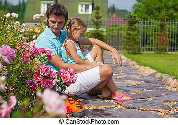Little cute girl and father relaxing in their garden