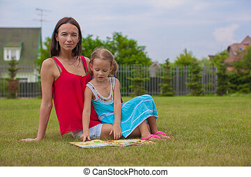 young mother and her cute daughter reading book and enjoying...