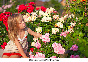 Little adorable girl sitting near colorful flowers in the...