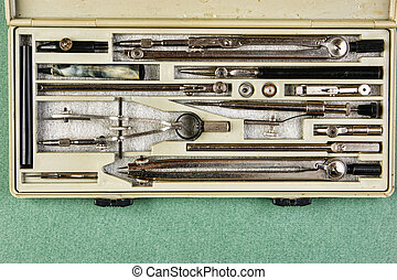 Old drawing tools in a box on a green background