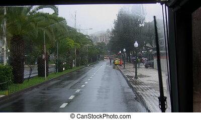 Rain in a tropical city - Tropical street view through the...