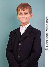 ?ute schoolboy show sign hello against school blackboard