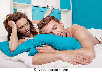 a couple lying in bed having a sex problems