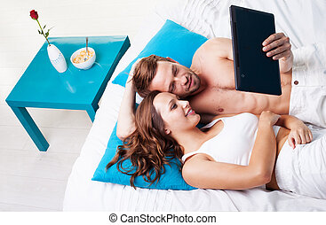 Young couple reading a tablet screen
