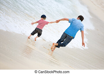 Family vacation. Happy father and son on the beach.
