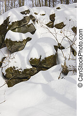 Rocks under snow in sunny winter day