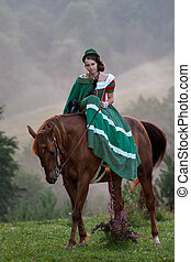 Girl riding equestrian classicism dress in fog