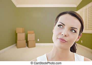 Young Woman Daydreaming in Empty Room with Boxes -...