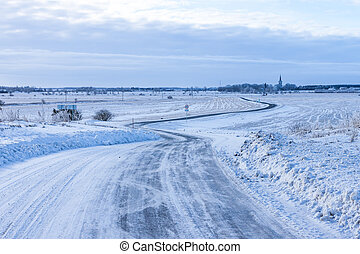 Countryside road through winter field with forest and church...
