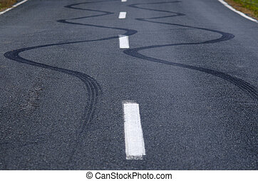 Winding skid marks of a vehicle on a street road