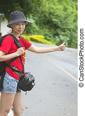 Hitchhiker women - A woman hitchhikes on the side of the...