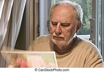 senior reading - elderly man reading his newspapers