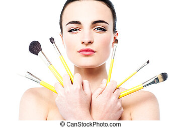 Beautiful girl holding makeup brushes set - Portrait of...