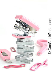 Pink stapler with office accessories on white background