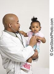 Girl and doctor - African-American male pediatrician holding...