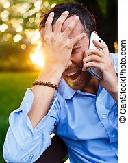 Frustrated handsome middle-aged man with mobile phone outdoors