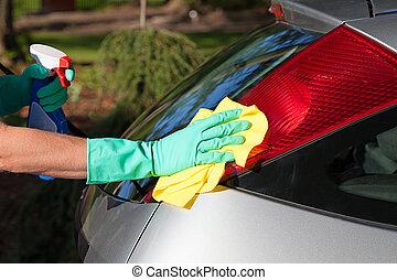 Car polishing - A man polishing a car with a rag