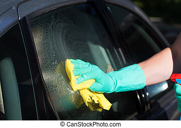 Car window washing - A man washing a cars window