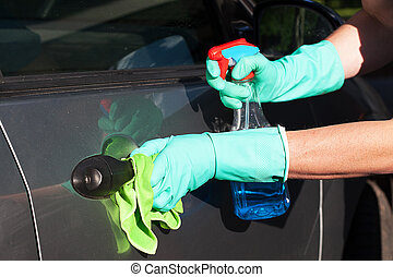 Car handle cleaning - A man cleaning a car handel using a...