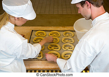 Bakers in bakery producing pretzels - Two bakers in bakery...