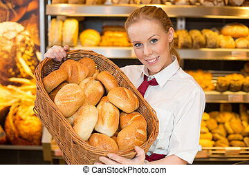 Shopkeeper in baker's shop presenting buns in a basket -...