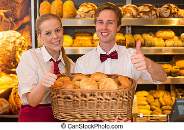 Bakers in bakery with basket full of bread - Bakers or...
