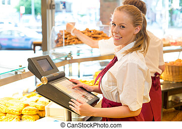 Cashier in bakers shop posing with cash register - Cashier...