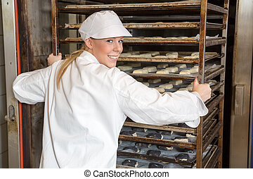 Baker pushing rack full of bread into the oven - Baker in...