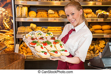 Shopkeeper in bakery showing sandwiches to customer -...