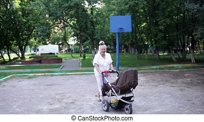 Grandmother walks with her grandson in the yard Camera...