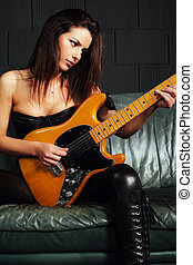 Beautiful guitarist sitting on couch