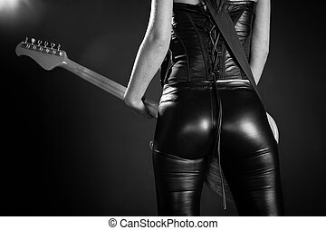 Sexy woman playing an electric guitar - Photo of the back of...