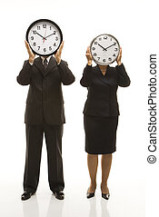 Businesspeople holding clocks. - Caucasian middle-aged...